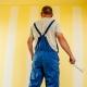 en man som målar med gul väggfärg inomhus