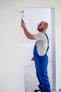 en man som applicerar vit målarfärg på väggan